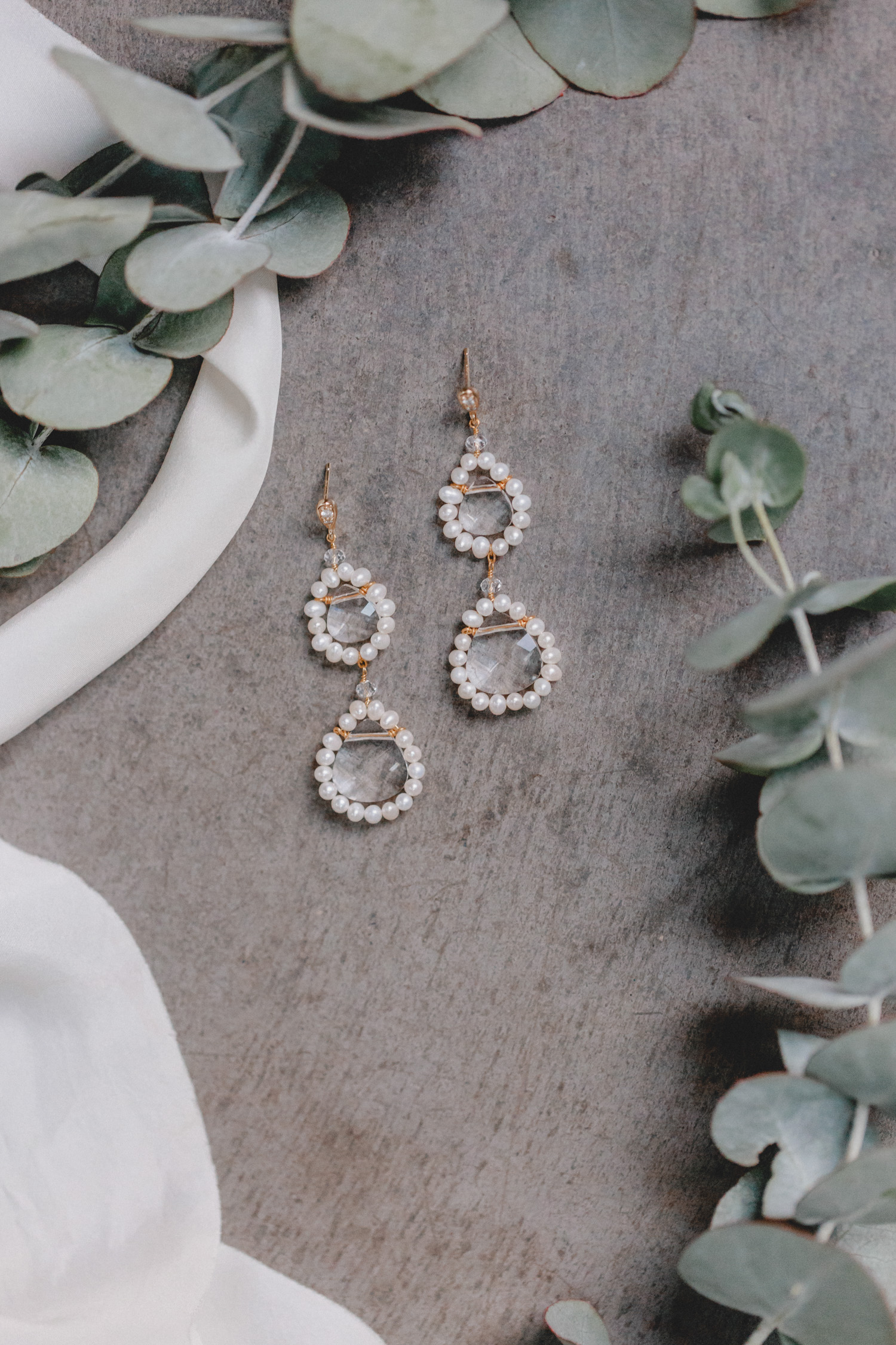 A true favourite piece of jewellery: these earrings impress with two intricately linked circles of high-quality freshwater pearls, each caressing a large, faceted Swarovski drop-shaped crystal.