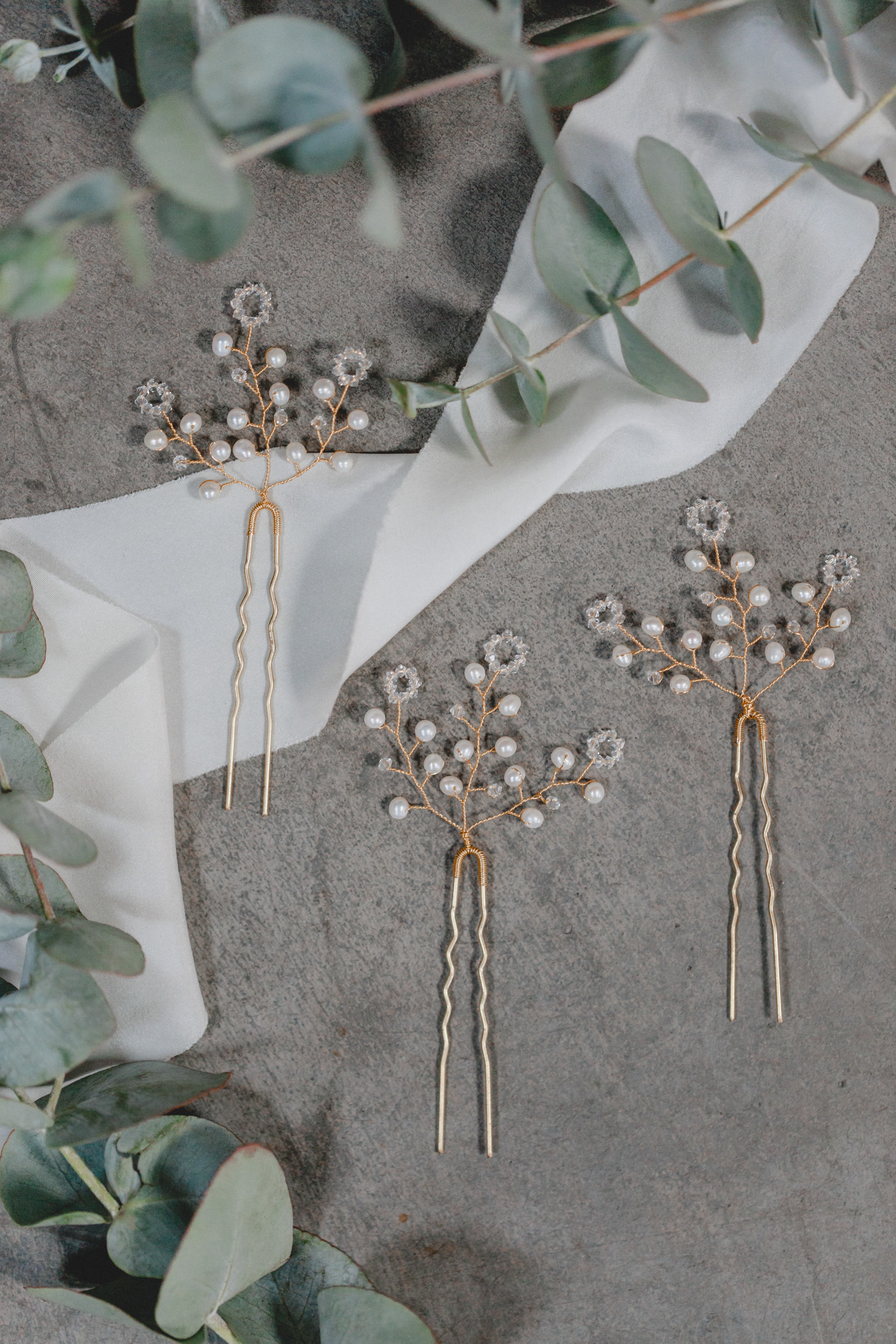 This intricately branched hairpin is crisscrossed by delicate shimmering freshwater pearls and glittering Swarovski crystals, which as a highlight at each end have been worked into a circular flower shape.