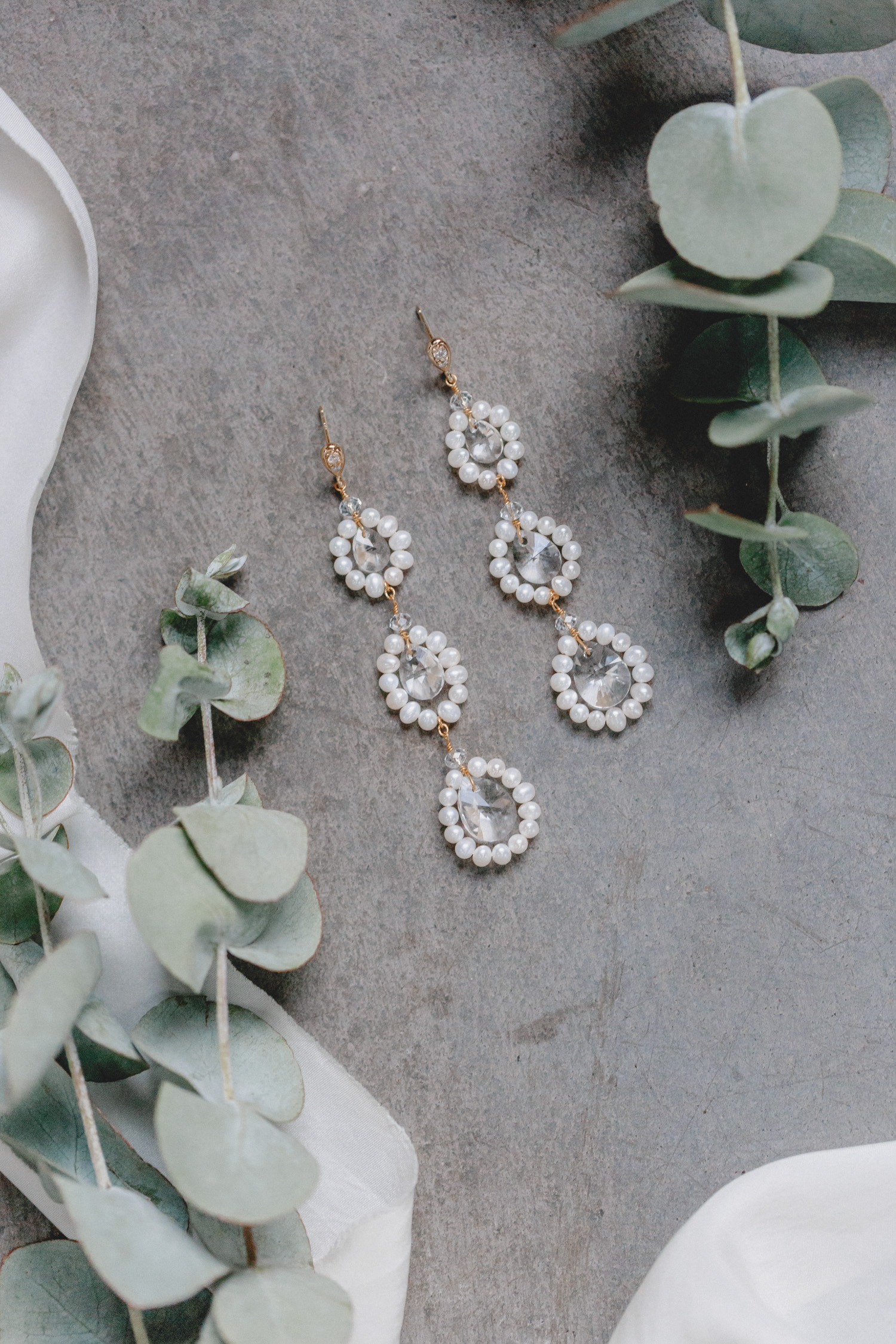 These opulent earrings unite three interconnected circles of shimmering freshwater pearls, each framing a sparkling, eye-catching Swarovski crystal of varying sizes.