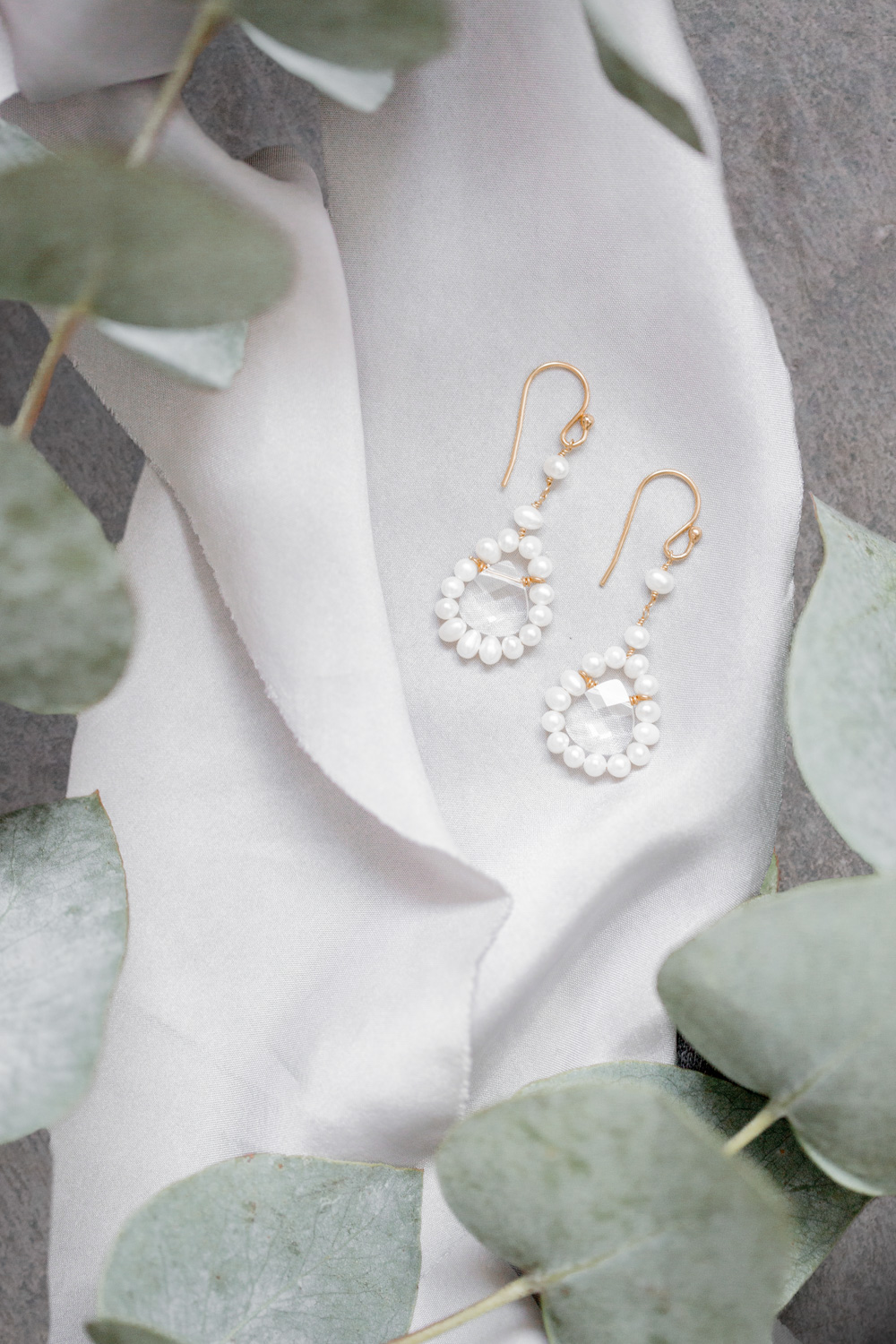 In these expressive earrings, a drop-shaped, faceted Swarovski crystal is framed by white freshwater pearls. Two small individual pearls provide a filigree silhouette and extra highlights at the top.